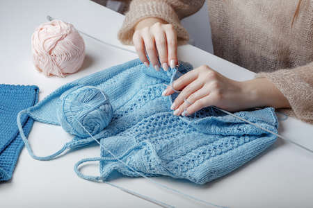 knitting sweaters of blue woolen yarn at the table
