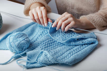 woman knits handmade woolen blue sweater on the table