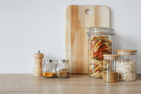 pasta and spices in the jars on the table Imagens