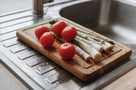 washed tomatoes and asparagus on the board