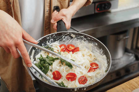 cooking fresh handmade pasta with red tomatoes Imagens