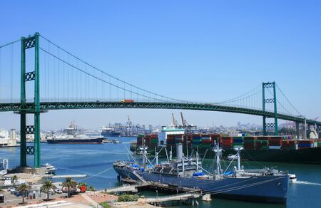 bustling: A bustling, warm climate shipyard is located beneath a bridge. Stock Photo