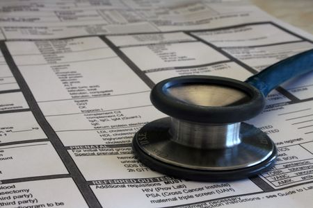 A medical requisition form for various lab results and tests is shown with selective focus near the front and a doctor's stethoscope resting on top.