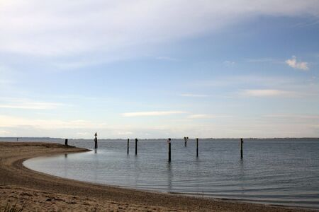 pilings: A peaceful ocean bay is shown with low tide.