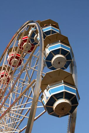 The top portion of a ferris wheel ride is caught against a blue sky background.