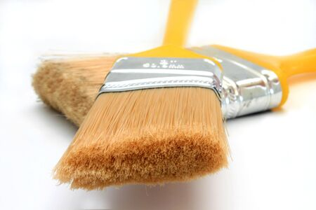 Two yellow-handled paintbrushes are crisscrossed and isolated on a white background. Stock fotó