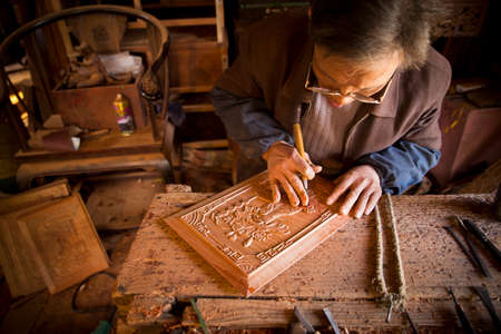 workbench: an old craftsmen carving on wood