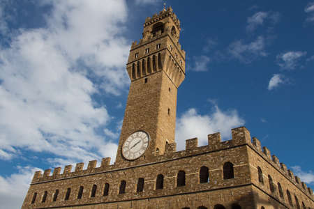 Italy, Florence - November 06 2016: view of the clock tower fragment of the Old Palace with blue sky on November 06 2015 in Florence Italy. Editorial
