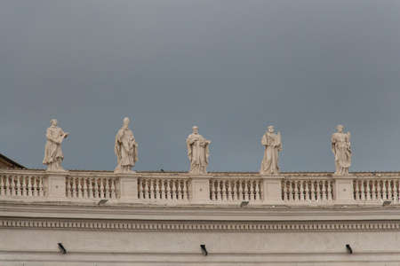 Italy, Vatican city - April 18 2017: the view of colonnade statues with rainy sky on background on April 18 2017, Vatican city state, Italy.