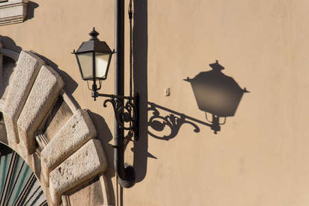 The view of the street lantern and its shadow in a sunny day.