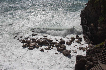 The view of the sea wave rolls towards stones. 写真素材