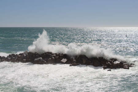 The view of horizon line over sea and a wave is crashing stones. 写真素材