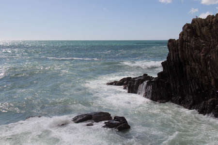 The view of seascape landscape with horizon line above sea and waves crashing on rocks.