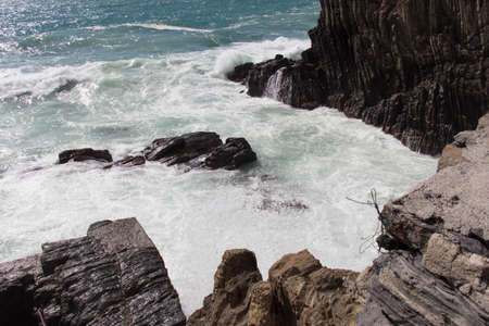 The view of the waves crashing on rocks.