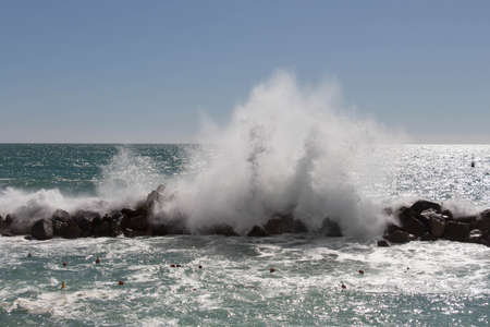 The view of the waves crashing on a group of stones.