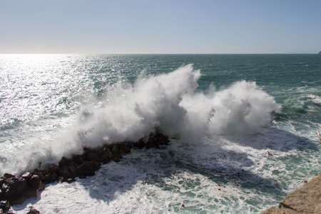 The view of seascape with horizon line over sea and wave is crashing stones.