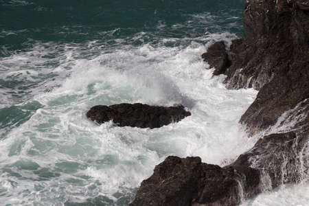 The view of the wave crashing on group of stones.