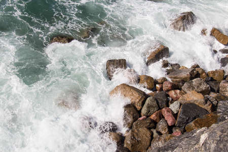 The view of the wave crashing on a group of stones.