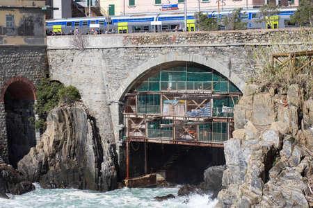 Riomaggiore, Italy - April 1 2018: the view of bridge and train station in Riomaggiore in the National Park of Cinque Terre on April 1 2018 in Liguria Italy.