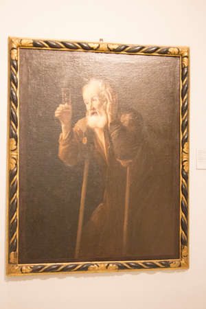 Italy, Brescia - December 24 2017: the view of the oil on canvas, Old man with an Hour glass, by Antonio Cifrondi in Brescia Museum on December 24 2017 in Brescia, Lombardy, Italy.