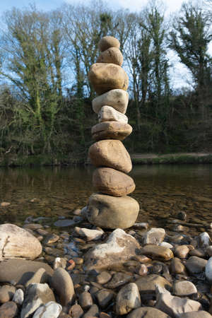 A stack of balanced stones next to a river.