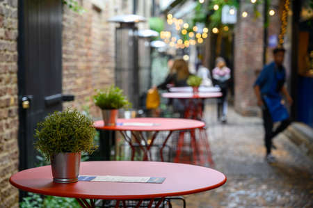 LONDON - SEPTEMBER 30, 2019: A row of empty tables on a cobbled street in an outdoor dining area of Camden Market, with people in the background