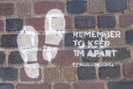 A painted sign on a cobbled floor reminding people to social distance and keep 1M apart due to the COVID-19 pandemic