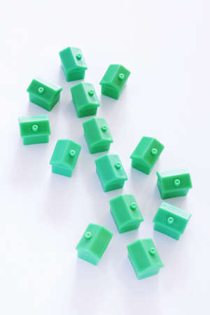 first time buyer: Dollar sign made from green model houses on white background