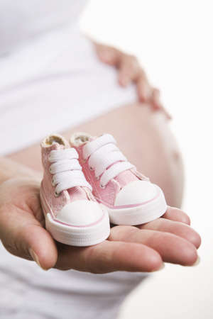 Pregnant woman holding pair of pink shoes for  girl