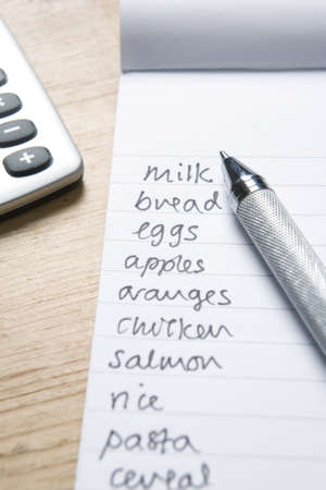 shopping list: Handwritten Shopping List With Pen And Calculatot Stock Photo