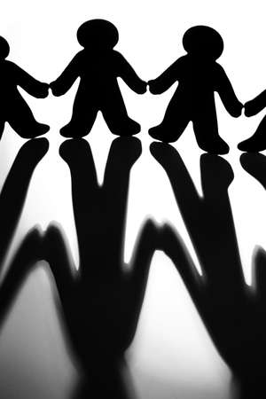 silhoutted: Black And White Image Of Silhoutted Figures Joining Hands To Illustrate Concept Of Support And Collaboration Stock Photo