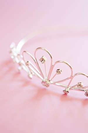 silver princess tiara often worn at weddings with jewels shot on pink background