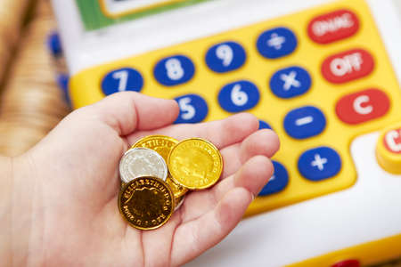 Child Playing With Toy Cash Register And Coins photo