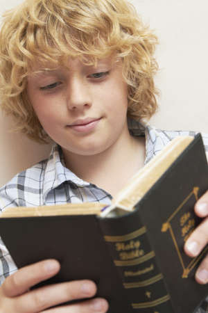 boy 12 year old: Boy Reading Bible In Bedroom