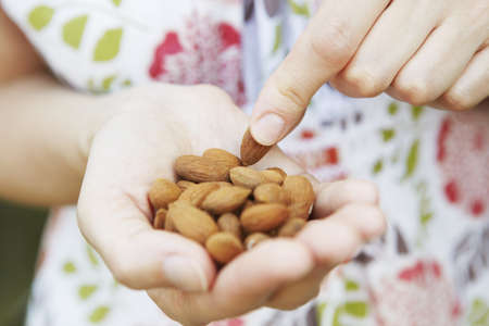 Woman Eating handful Of Almonds