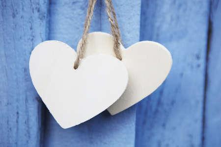 corazones azules: Dos corazones de madera sobre fondo azul