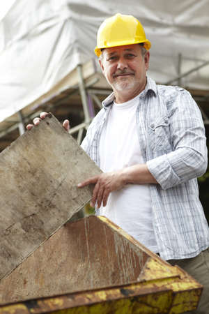 rennovation: Builder Putting Rubbish In Skip