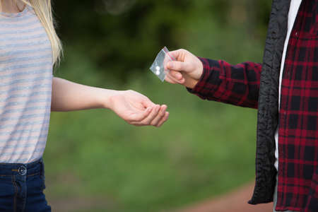 teenage guy: Teenage Girl Buying Drugs In Playground From Dealer