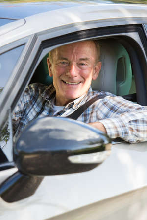 old: Portrait Of Smiling Senior Man Driving Car