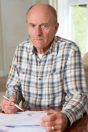 concerned: Concerned Senior Man Reviewing Domestic Finances Stock Photo