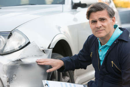 adjuster: Auto Workshop Mechanic Inspecting Damage To Car And Filling In Repair Estimate Stock Photo