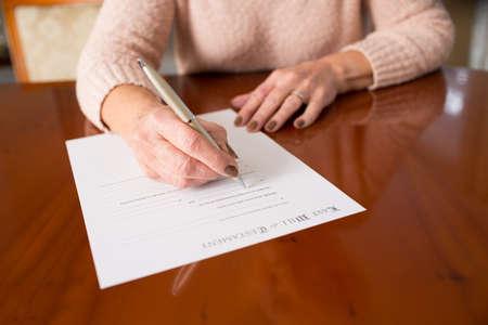 firmando: Mujer mayor firma de testamento en el hogar Foto de archivo