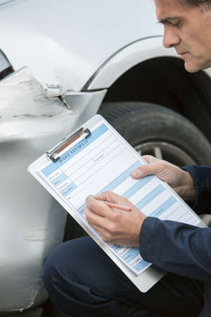 filling in: Auto Workshop Mechanic Inspecting Damage To Car And Filling In Repair Estimate Stock Photo