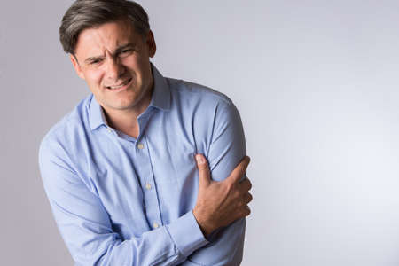 Studio Of Mature Man Clutching Arm As Warning Of Heart Attack