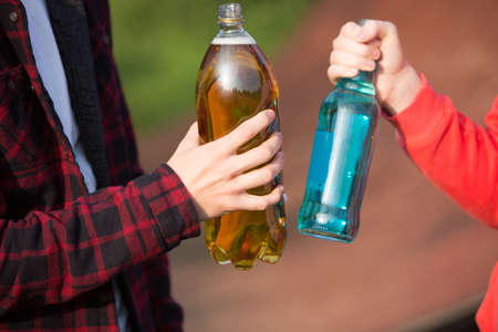 teenager: Close Up Teenagers Drinking Alcohol Together Stock Photo