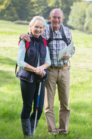 walking pole: Active Senior Couple On Walk In Countryside Together