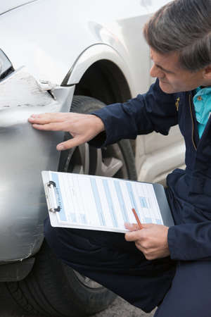 cars on road: Auto Workshop Mechanic Inspecting Damage To Car And Filling In Repair Estimate Stock Photo