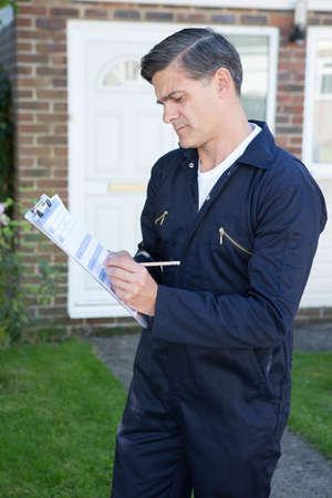 Workman Preparing Estimate For Work On House Exterior