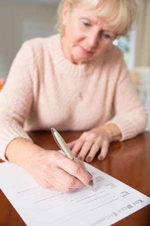 Mujer mayor firma de testamento en el hogar Foto de archivo