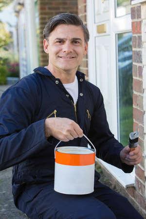 brocha de pintura: Hombre celebración de pincel y la lata de pintura exterior de la casa